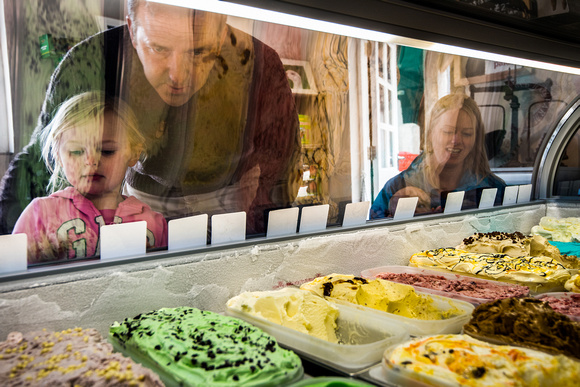 A family looking into an ice cream cabinet to choose their favourite flavour
