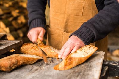 Baker slicing a baguette