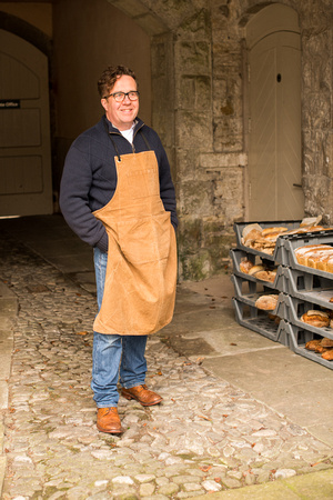 A baker stood by trays of bread